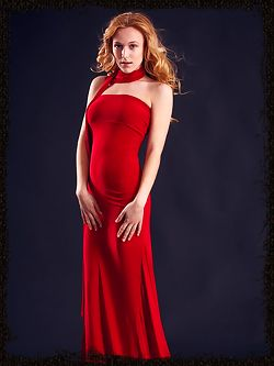 Wearing stylish red dress that hugs her body curves, her red hair elegantly cascading into curls, Aislin's exotically girlish beauty with womanly allure can make any man down to his knees.