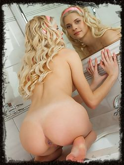 Blondie Charmane flaunts her slender, tight body and sweet pussy as she poses on the sink.