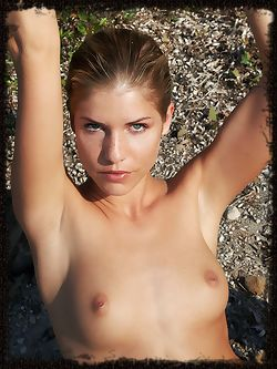 Iveta B's delicate, nubile beauty emanates from the rugged coastal surrounding.