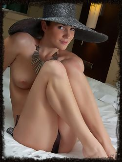 Wearing a broad brimmed hat, a chunky piece of necklace, and a sheer black panty, Veranda exudes elegance as well as lusty romance as she sprawls enticingly on the bed.